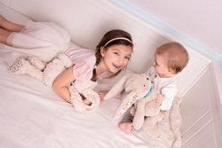 Dziewczynka i dziecko bawią się szumiącymi misiami Królikami Mruumi, prezentem pod choinkę